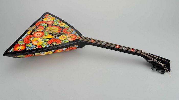 Balalaika - Saiteninstrument mit Triangelform mit Korpus, verziert mit drei unterschiedliche Arten von Blumen, schwarzer Griff