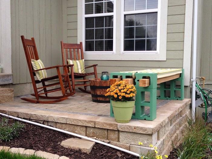haus mit terrasse - zwei braune stühle mit grünen kissen - blumentopf mit orangen blumen - eine grüne gartenbank aus grünen pflanzsteinen