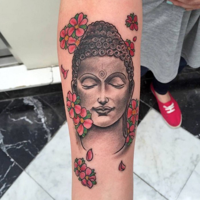 tattoos mit bedeutung, tätowierung mit buddha-motiv am unterarm, rosa kirschblüten