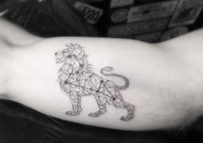 eine tattoo mit einem schwarzen löwe und einem schwarzen sternbild mit kleinen schwarzen sternen