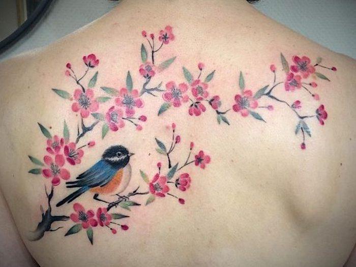 tattoo kirschblüten, rosa blüten in kombination mit vogel, tattoo am rücken