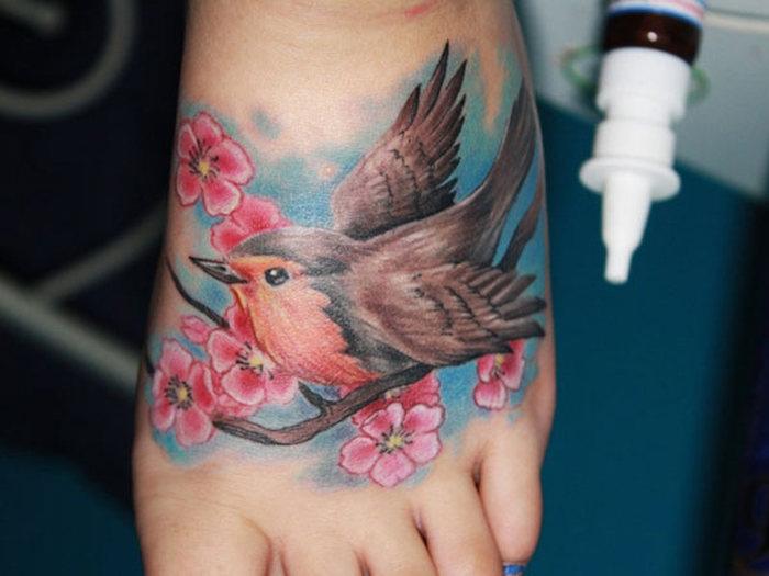 tattoo kirschblüten, bauner vogel auf zweig, farbige tätowierung am fuß