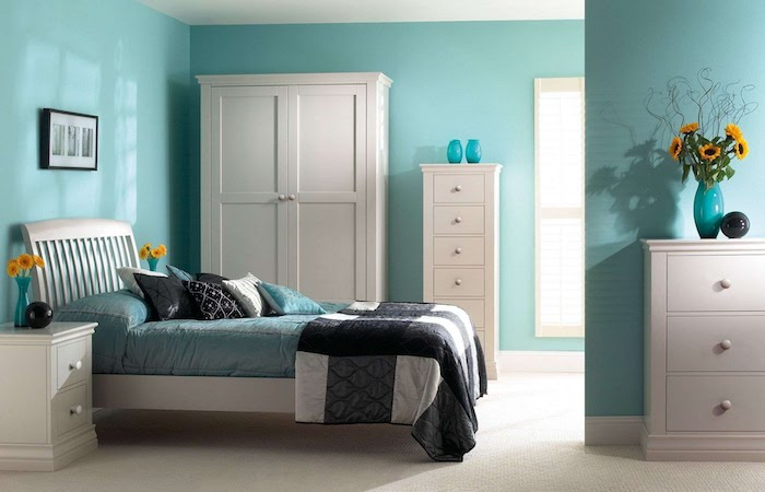 schöne Zimmer mit blauen Wänden, einem weißen Schrank, bunten Bettwäschen