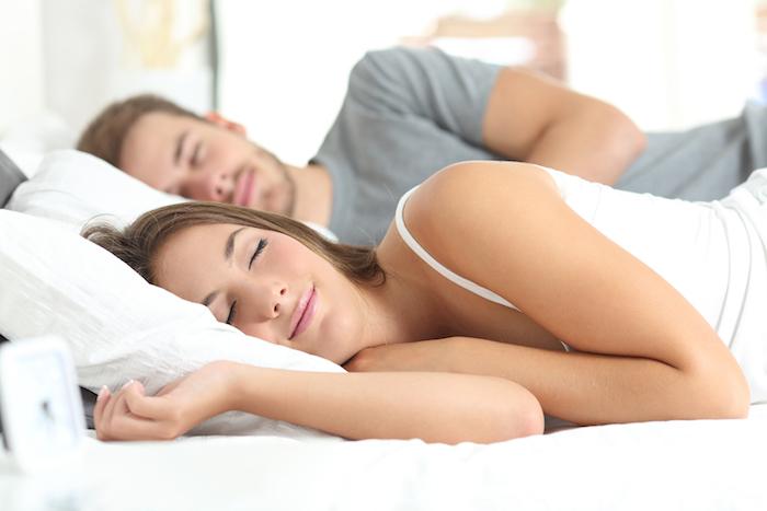 liebespaar - eine junge schlafende frau - ein bett mit einem weisen kissen