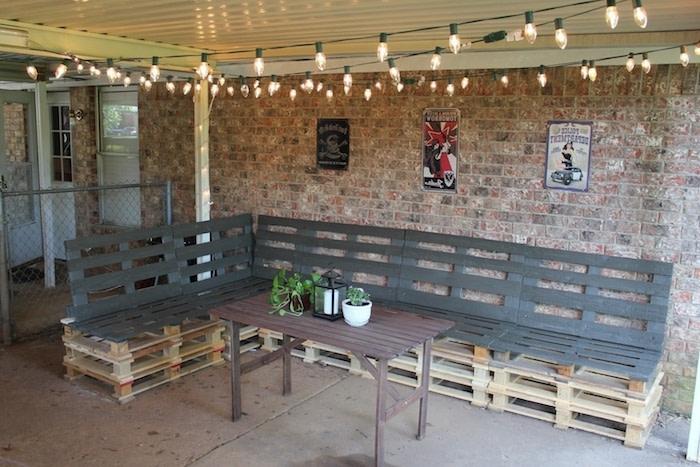 glühbirnen und eine langen gartenbänke aus alten europaletten - brauner tisch aus holz - blumentopf mit grünen pflanzen