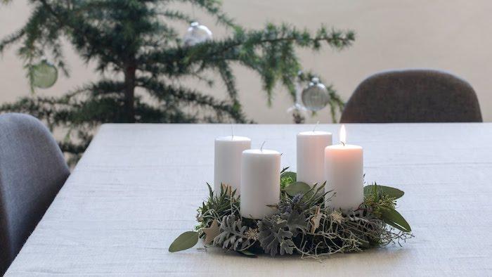 ein tisch mit einem kleinen adventskranz mit vier weißen kerzen und mot pflanzen mit grünen blättern