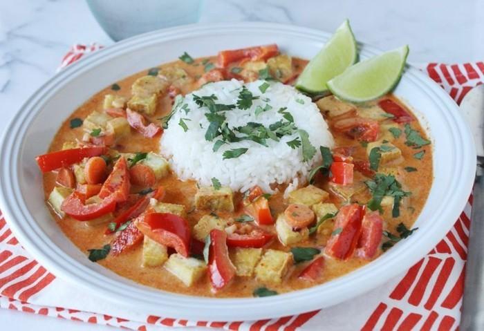 tofu rezept teller voll mit leckerer soße tofu rezept mit paprika tomatensoße sahne und frische kräuter limetten zitrone und reis in der mitte