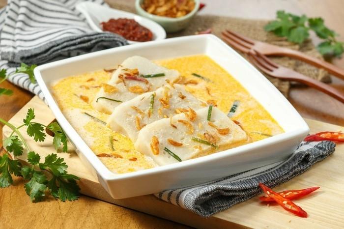 suppe mit tofu stücken servieren milchsuppe kräuter petersilie quadratische schüssel holzgabel paprika chilli