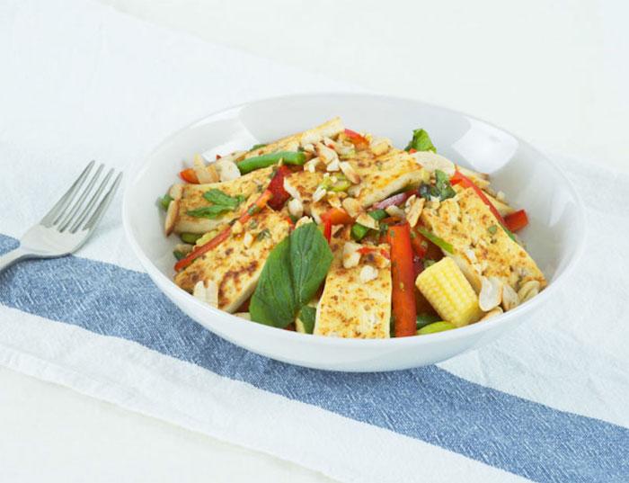 tofu rezept für einen schmackhaften salat mais blattsalat erdnüsse gabel auf dem tisch tischdecke weiß blau