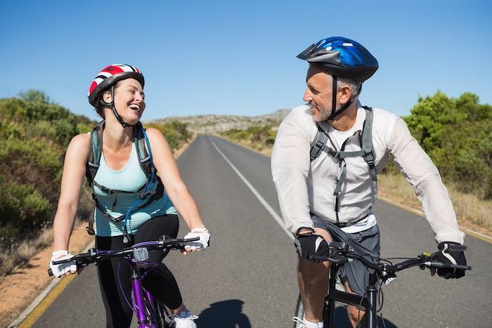 rad fahren und lachen kalorien verbrennen mann und frau fahren fahrrad auf der straße bikes kopfschutz