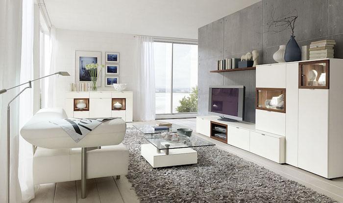 wohnwand weiß großer weißer schrank auf dem sich der fernseher befindet flauschiger teppich glastisch sofa