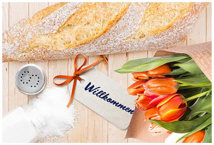 Glückwünsche zum Einzug - Esstisch aus Holz mit einer frisch gebackenem Ciabatta, kleine graue Willkommen-Karte mit einem runden Loch und einem orangen Band, ein offener Salzstreuer mit einem Metalldeckel , der kleine runder Löcher in der Form eines S haben, ein Tulpenstraus aus orangen und weißen Tulpen mit dekorativem Blumenstrauß-Papier mit kleinen weißen Buchstaben