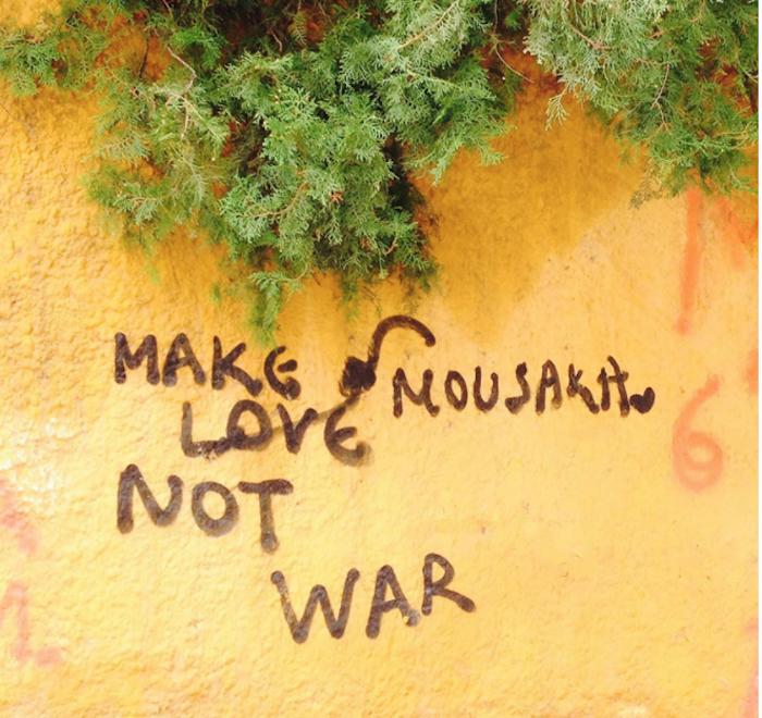griechenland weise worte auf der wand wandgrafitti grafiti graffiti grafitti athen grieche griechenland gelbe wand aufschrift in braun grüne pflanzen