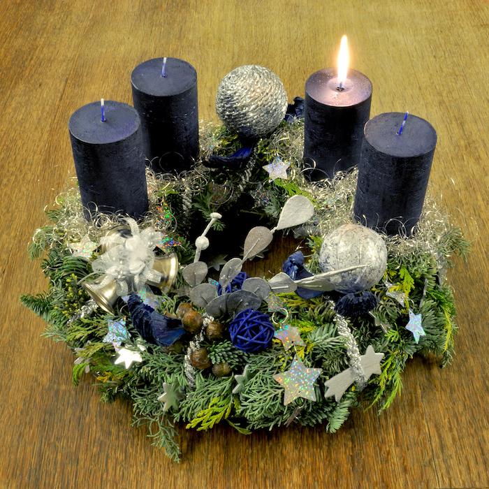 ein adventskranz mit vier kleinen blauen kerzen, mit grünen pflanzen mit grünen blättern und kleinen sternen und bällen