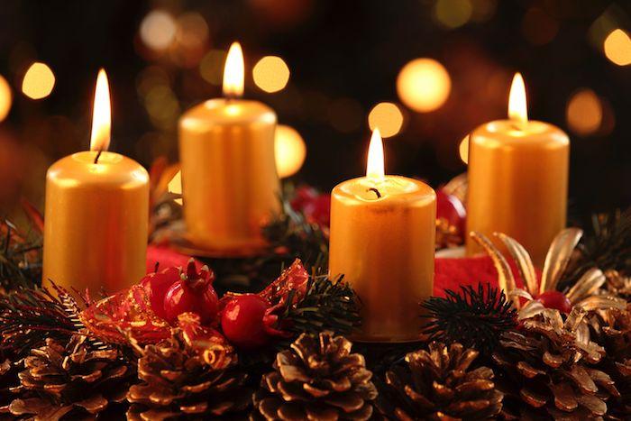 weihnachtsdekoration mit einem adventskranz mit kleinen braunen zapfen, gelben kerzen und ästen mit grünen blättern
