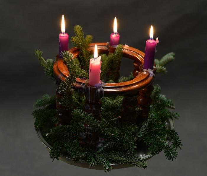 einen kleinen adventskranz mit ästen und drei lila kerzen und einer pinken kleinen kerze
