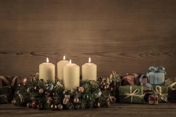 vier kleine weiße kerzen, kleine geschenke mit band - ein adventskranz mit kleinen bällen und braunen zapfen