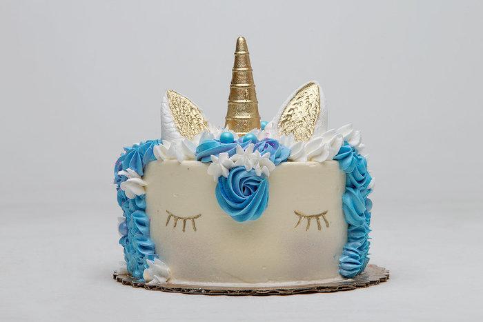 eine idee füreinhorn kuchen - hier ist eine weiße einhorn torte mit einer blauen mähne und mit einer blauen rose und mit einem goldenen langen horn - idee für einhorn kuchen deko