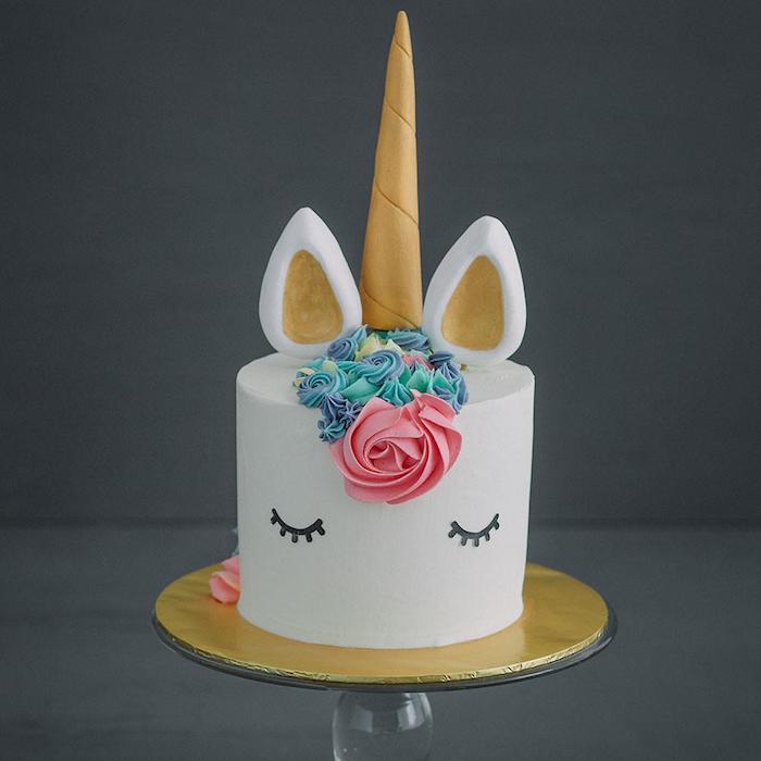 einhorn fondant torte mit einem weißen einhorn mit schwarzen augen, einer großen pinken rose und einer blauen mähne und goldenen ohren und einem goldenen gelben horn