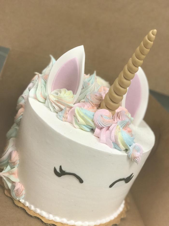 hier ist eine idee für einhorn kuchen - eine weiße torte mit einem großen gelben horn und mit schwarzen augen und mit kleinen weißen ohren, pinken ohren - möhne aus einer regenbogenfarbenen sahne