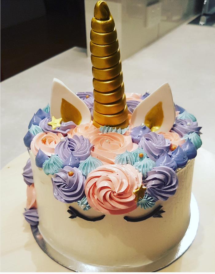 eine einhorn torte mit einem weißen einhorn und mit einer mähne aus pinken, lila und blauen rosen aus sahne und mit kleinen gelben sternen und mit einem großen goldenen horn