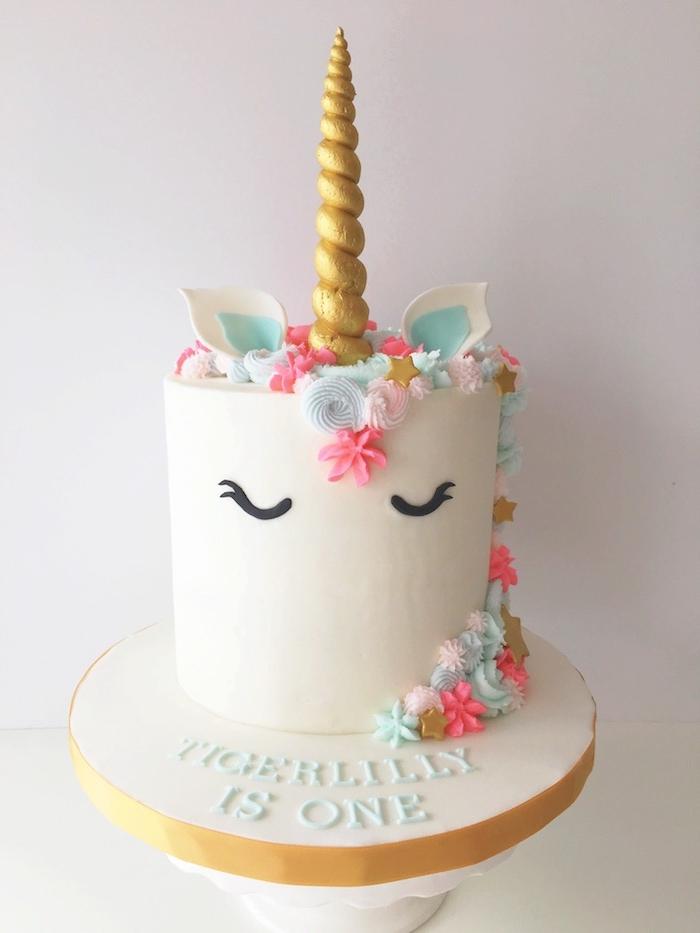 hier ist eine idee für eine weiße einhorn torte mit einem weißen einhorn mit schwarzen augen und mit pinken und blauen blumen und einem goldenen großen horn und kleinen blauen ohren