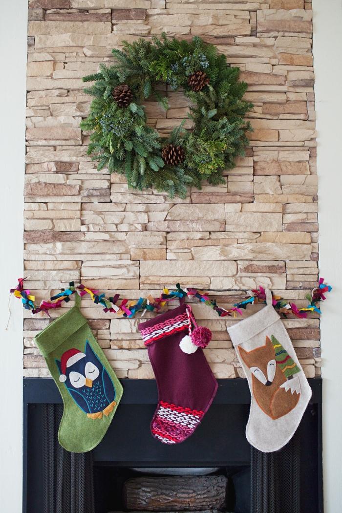 Großer Weihnachtskranz aus Tannenzweigen und Zapfen, drei Weihnachtsstrümpe und bunte Girlande, Weihnachtsdeko im Wohnzimmer