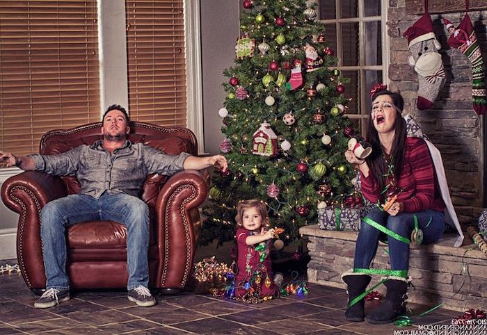 eine lustige Familie um dem Tannenbaum, der Vater sieht erschöpft aus, die Mutter ist im Geschenkband umhüllt, nur die kleine Prinzessin ist glücklich - Weihnachtsfotos