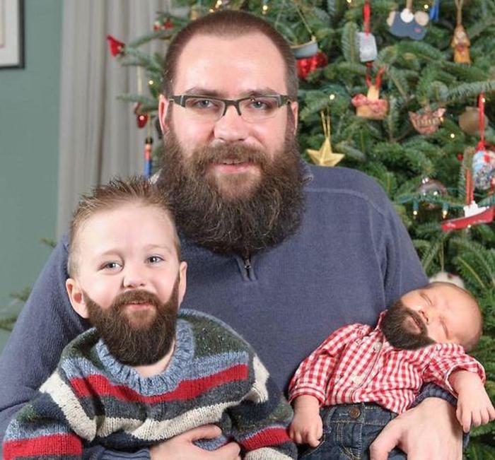 Weihnachtsfotos - Vater und zwei Kinder alle haben denselben Bart vor dem Tannenbaum