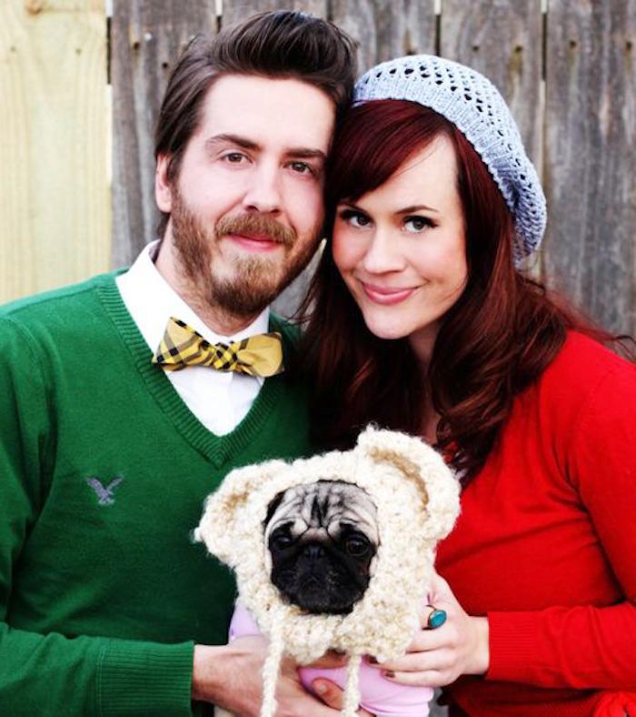 eine Frau und ein Mann, die sein Hund als Baby zeigen - Weihnachtsfotos