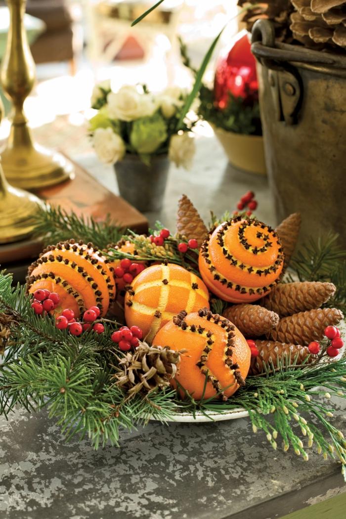 Weihnachtsdeko aus Orangen, Zapfen und Tannenzweigen, schöne Idee für Weihnachtstischdekoration