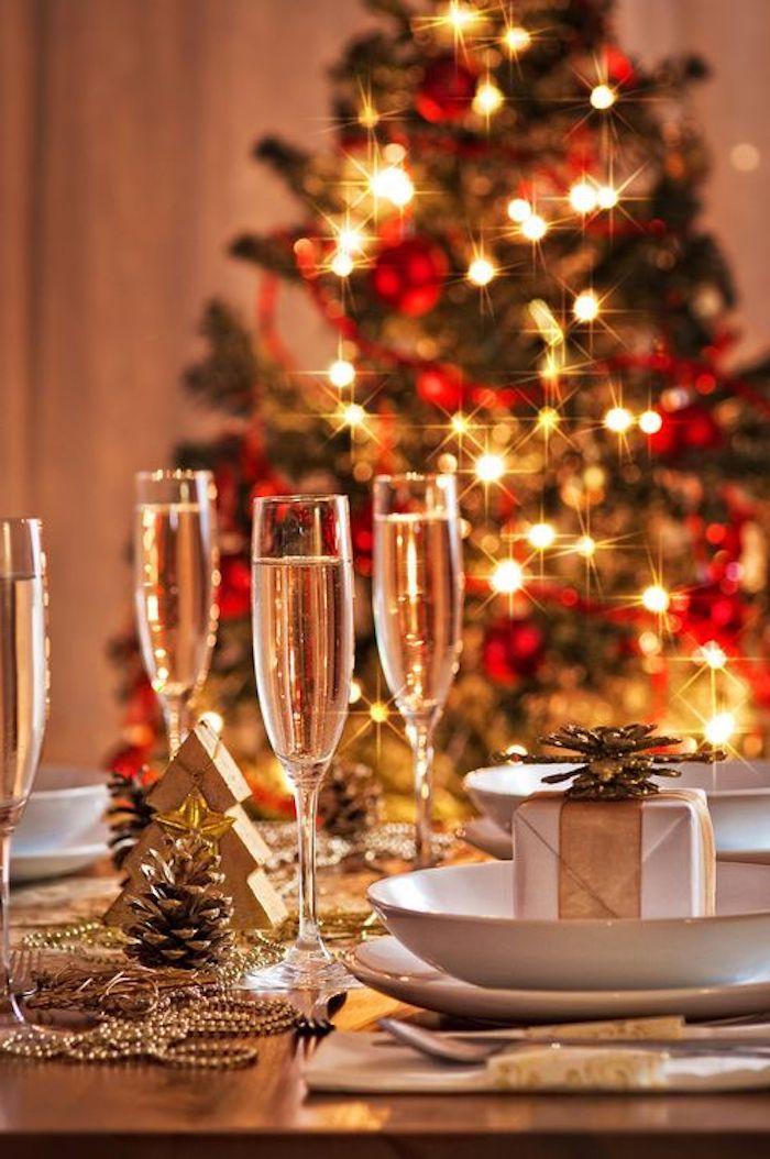 deko weihnachten tischdekor ideen zum gestalten drei gläser voll mit weißwein perlen als deko auf dem tisch weihnachtsbaum im hintergrund