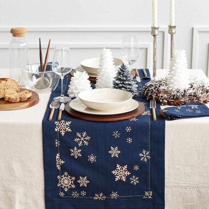 dekoideen weihnachten weiße hauptdecke mit dunkelblauen kleineen decken darauf blaue servietten und weiße schneeflocken als deko motive ideen feine weihnachtliche deko