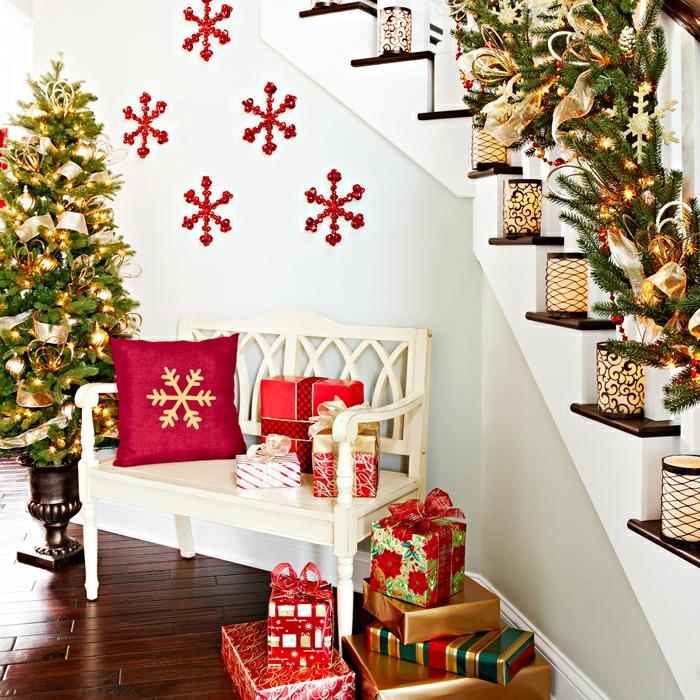 Wunderschöner Christbaum mit viel Schmuck, rote Schneeflocken an der Wand, schön verpackte Geschenke auf dem Boden, Girlanden aus Tannenzweigen, Weihnachtsatmosphäre zu Hause