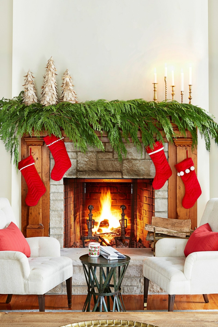 Das Wohnzimmer zu Weihnachten dekorieren, Weihnachtsstrümpfe und Tannenzweige am Kamin, goldene Christbäumchen und Kerzenhalter