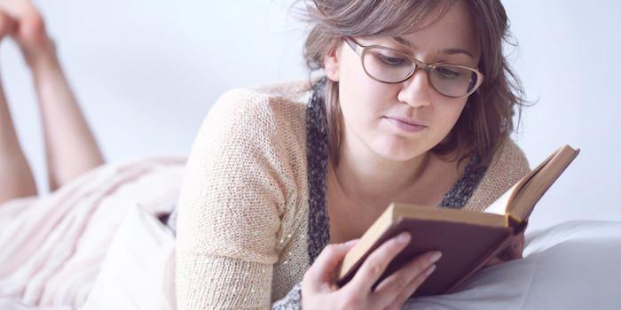 geschenkideen beste freundin buch lesebrille eine frau liegt auf dem coach und liest ihr lieblingsbuch mit lesebrille