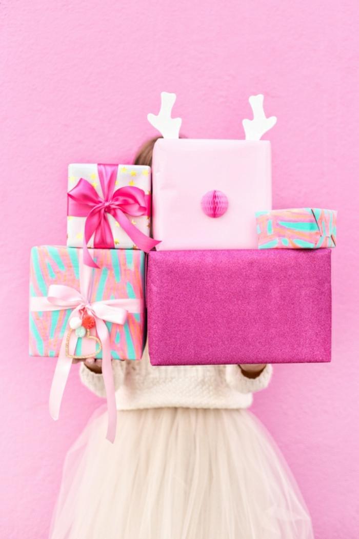 Weihnachtsgeschenke in rosafarbenen Verpackungen, mit schönen Bändern verziert, Rudolph mit der roten Nase aus Papier