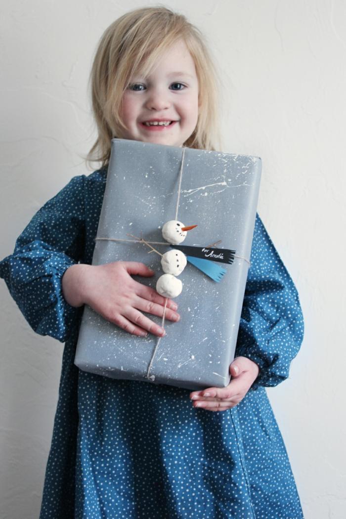 Schneemann aus Plastilin basteln und Weihnachtsgeschenk verpacken, blondes Kind mit großen schwarzen Augen