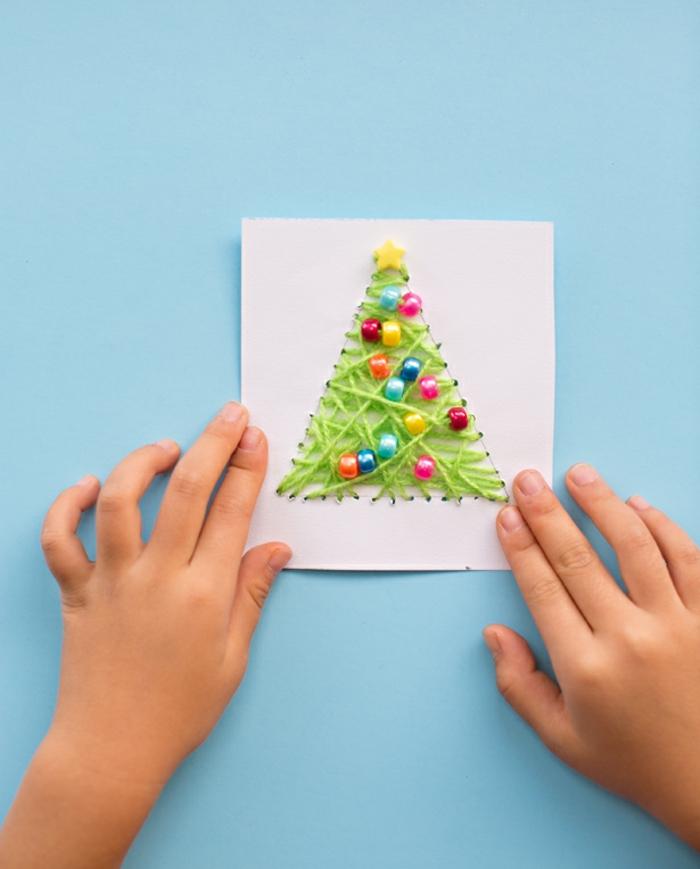 Weihnachtskarten mit Kindern basteln, Weihnachtsbaum aus grünem Garn und bunten Holzperlen, Ideen für Weihnachtsbasteln