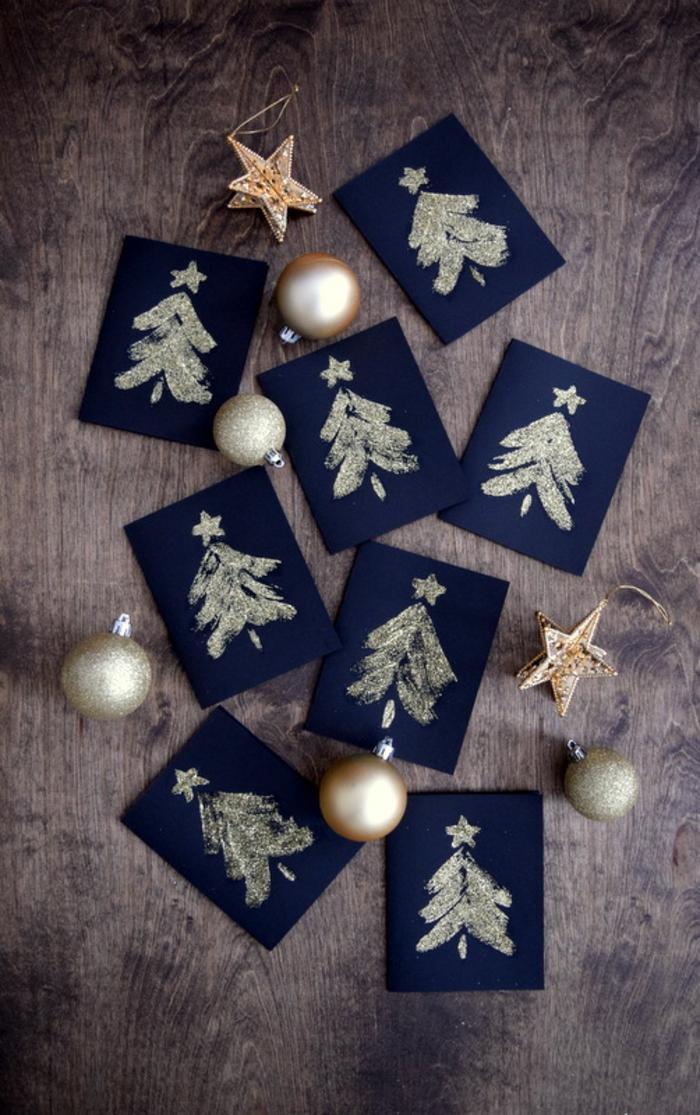 Weihnachtskarten selber basteln, goldene Christbäumchen auf schwarzem Grund, Kleber auftragen, mit Glitzer besprühen