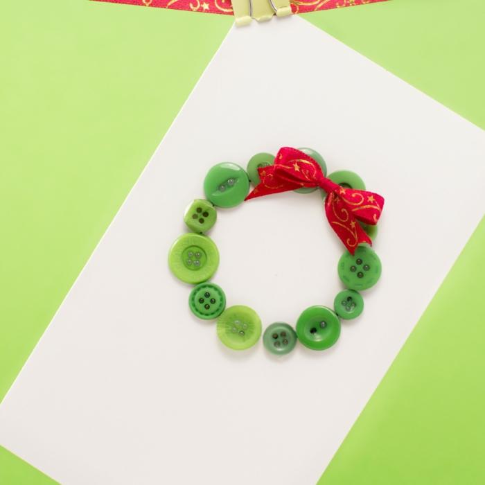 Weihnachtskarten basteln, Weihnachtskranz aus kleinen grünen Knöpfen und rotem Dekoband