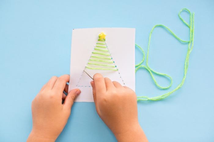 DIY Idee für Kinder, Weihnachtskarten selber machen, Weihnachtsbaum aus grünem Garn und bunten Holzkugeln