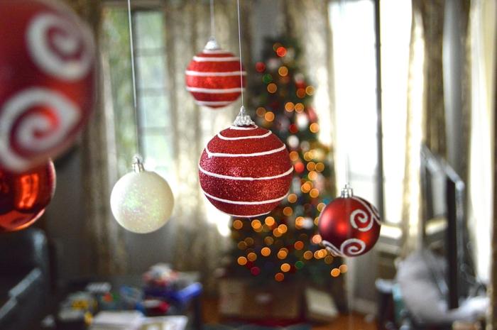 Weiße und rote Weihnachtskugeln mit Glitzer besprüht, an der Decke aufgehängt, Idee für Weihnachtsdekoration