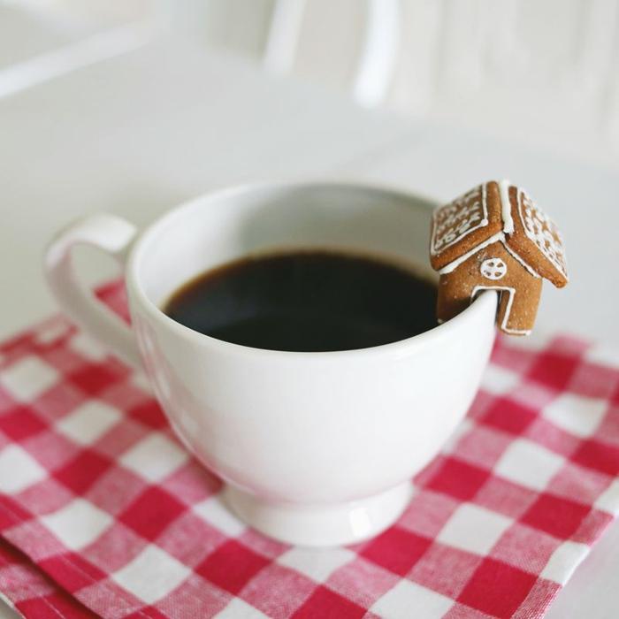 Lebkuchenhäuschen an Tasse, Kaffee trinken, karierte Decke darunter, Weihnachtsatmosphäre überall