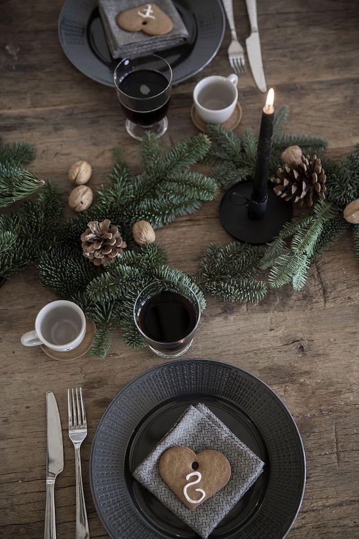 weihnachtliche tischdeko massivholztisch grüne zweige zapfen kerze walnüsse teller