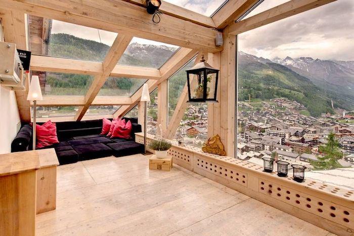 wohnung einrichten ideen einzigartige ausblicke aus einer dachwohnung gemütliches ambiente schwarzes sofa rote kissen ausblick über die stadt