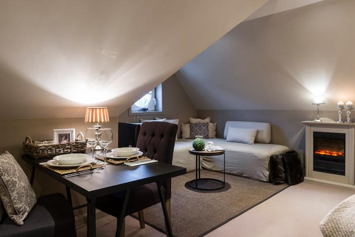wohnung einrichten kleine mansardenwohnung wohnzimmer mit essbereich kamin und großem sofa stehlampe