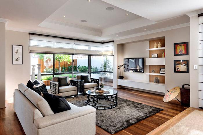 tv paneel buntes wohnzimmer wohnbereich zu hause sofa weiß mit schwarzen kissen runder tisch teppich wanddeko