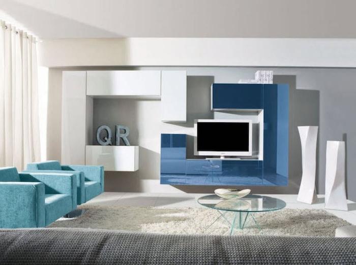 schrankwand fernsehwand in blau und weiß glastisch im zentrum des zimmers zwei blaue sessel