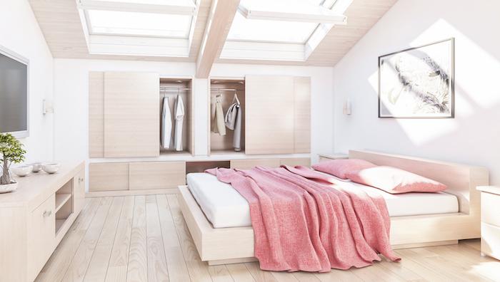 wohnung einrichten großes und helles schlafzimmer mit fesntern am dach dachfenster natürliches licht zulassen rosa bettdecke fernseher wandbild deko